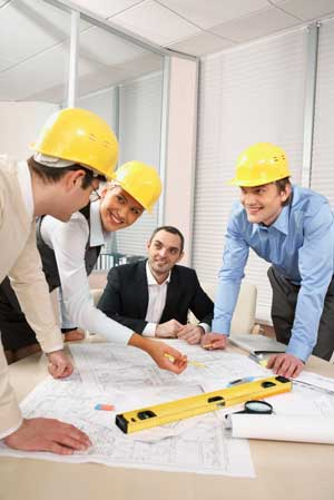 Group of construction executives looking at blue prints