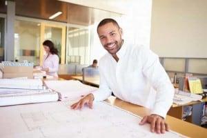 man at table looking at blueprints