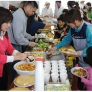 a group of neighbors serving food at a gathering