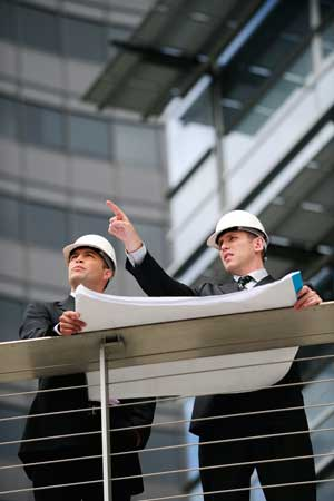 Two business men wearing hard hats and reviewing plans
