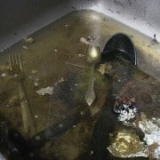 A clogged kitchen sink filled with dirty water and utensils