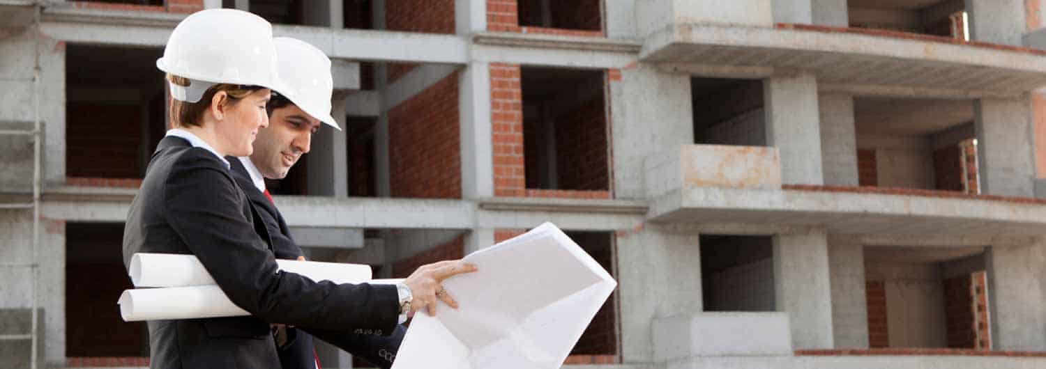 Two business executives wearing hard hats and looking at building plans in front of a building