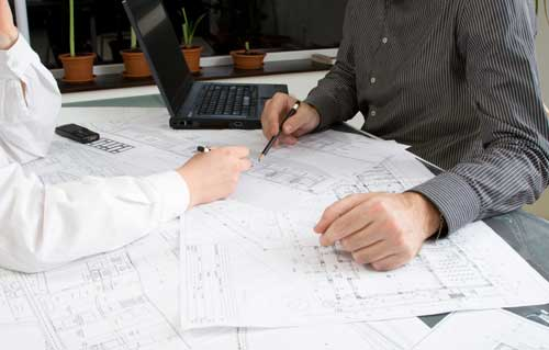 Two people looking over building plans