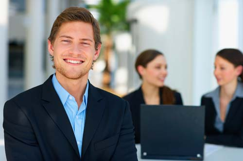 man in office environment smiling