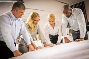 Four experts looking at blueprints