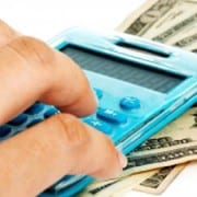 A person using a calculator with money set underneath it