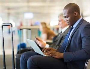 Man sitting at airport and doing work on his laptop