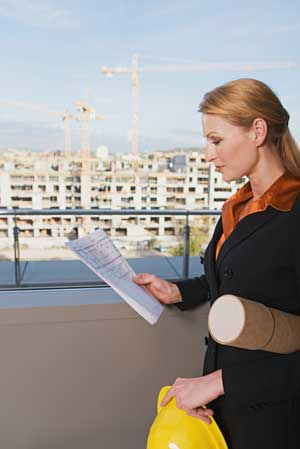 professional woman holding paper in front of building under contruction