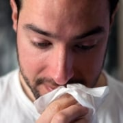 man suffering from allergies and wiping nose