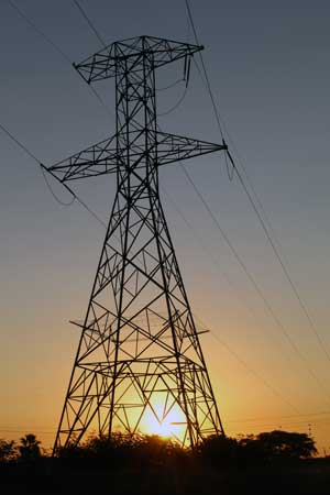 an electrical tower with the sun behind it