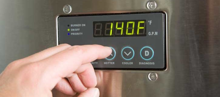 a person's fingers touching control panel of tankless water heater