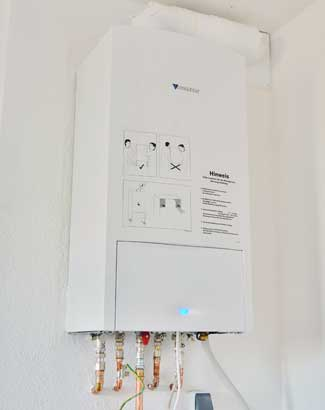 white tankless water heater attached to a wall