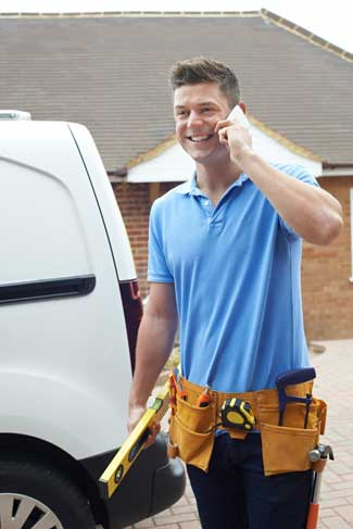 A building contractor talking on cell phone standing next to white van