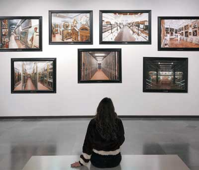 Woman sitting in front of paintings at art gallery
